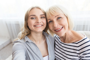 Senior mother and daughter taking selfie at home