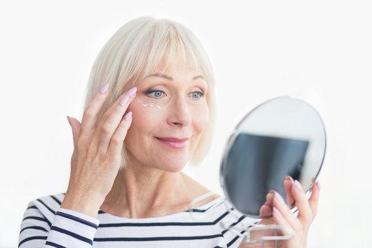 Happy senior woman applying eye anti-wrinkle cream