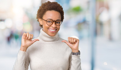 Young beautiful african american woman wearing glasses over isolated background looking confident with smile on face, pointing oneself with fingers proud and happy.