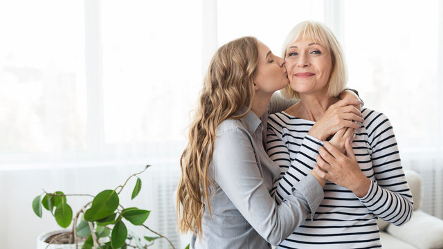 Young daughter kissing senior mother on the cheek