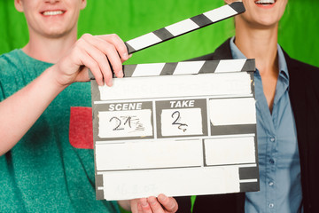 Assistant holds movie slate into the camera to start the production of a video piece