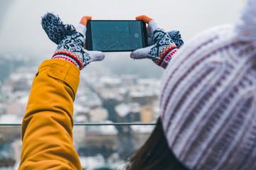 tourist woman taking selfie of winter city