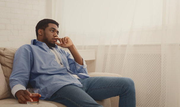 Young black man drinking alcohol at home feeling lonely