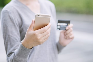 close up young female hands holding credit card and using mobile smart phone. Online shopping purchase Sell or Payment. Technology Pay online finance concept.