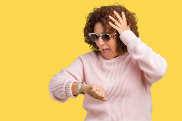 Beautiful middle ager senior woman wearing pink sweater and sunglasses over isolated background Looking at the watch time worried, afraid of getting late