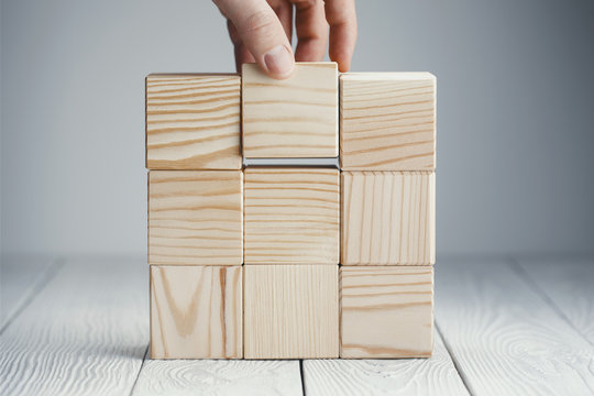 Hand putting the cube on other wooden cubes on neutral background
