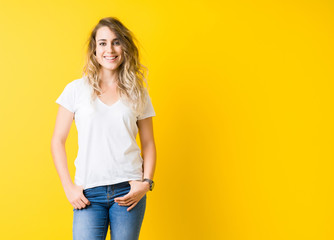 Beautiful young blonde woman smiling standing over isolated yellow background