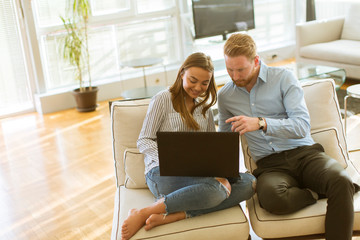 Couple using laptop in the room