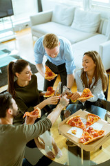 Young people eating pizza and drinking cider in the modern interior