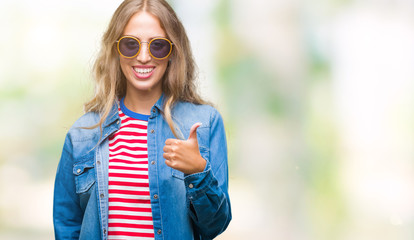 Beautiful young blonde woman wearing sunglasses over isolated background doing happy thumbs up gesture with hand. Approving expression looking at the camera with showing success.