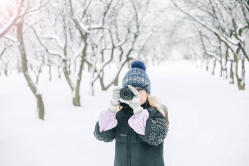 girl photographer in the winter in the snow-covered park photographs nature. woman in winter clothes.