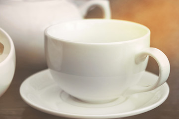 White empty porcelain mug and ceramic teapot in cafe in sunlight. Template glass kitchenware for designer use