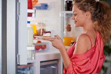 Woman taking cheesecake from fridge full of groceries for breakfast. Unhealthy eating concept. Fridge full of groceries.