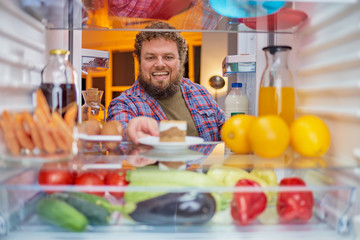 Man standing and taking gateau from fridge.  Picture taken from the inside of fridge.