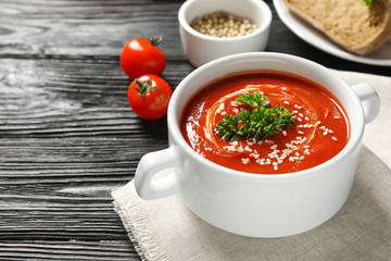 Dish with fresh homemade tomato soup and space for text on wooden table