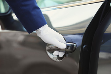 Closeup view of chauffeur opening car door