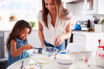 Young Hispanic girl making cake in the kitchen with her mum, waist up