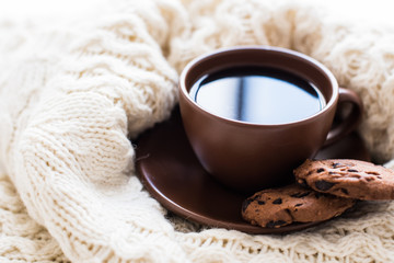 Brown cup of coffee and sweets on white blanket