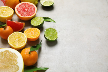 Different citrus fruits on grey background. Space for text