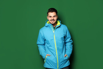Young man wearing warm clothes on color background. Ready for winter vacation