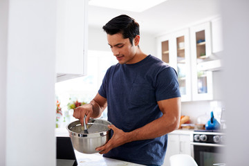 Millennial Hispanic man preparing cake mixture, following a recipe on a tablet computer, close up