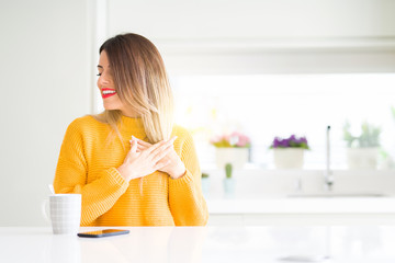 Young beautiful woman drinking a cup of coffee at home smiling with hands on chest with closed eyes and grateful gesture on face. Health concept.