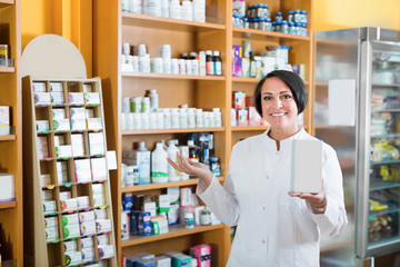 Glad mature female seller with  box in pharmaceutical  store