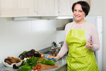 Portrait of cooking brunette housewife in apron