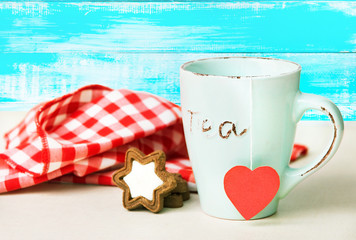 Mug with a heart and a cookie on a table festive concept
