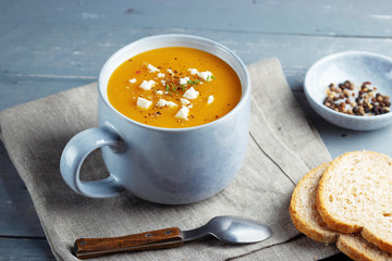 Spicy pumpkin and sweet potatoes soup in big ceramic mug garnished with feta cheese.