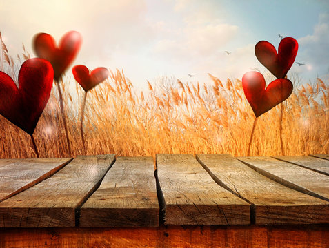 Wooden table with landscape and hearts. Valentines background