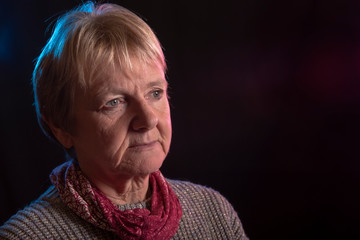 Portrait image of a mature woman on a black background, taken with copy space