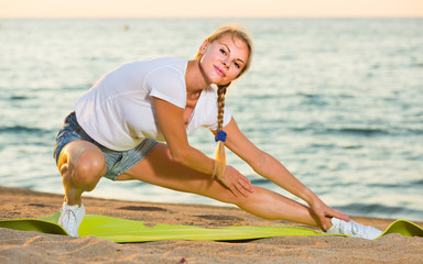 Smiling adult woman in white T-shirt is practicing stretching