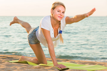 Smiling adult woman in white T-shirt is doing excercises on endurance