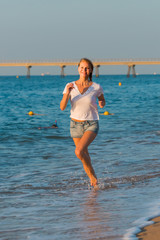 Smiling adult woman in white T-shirt is jogging on the beach