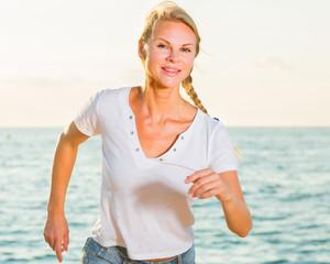 Sportswoman is jogging on the beach