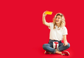beautiful girl with a gift makes selfie on the phone on an isolated red background. Valentine's day, holidays concept