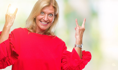 Middle age blonde woman over isolated background shouting with crazy expression doing rock symbol with hands up. Music star. Heavy concept.