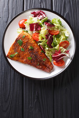 Serve baked pike fillet and fresh salad close-up on a wooden table. Vertical top view