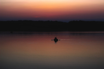 Silhouette of a man which floating on a boat on the sea at sunset time.