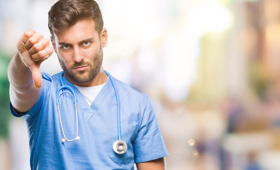 Young handsome doctor surgeon man over isolated background looking unhappy and angry showing rejection and negative with thumbs down gesture. Bad expression.