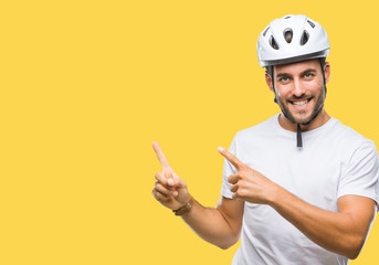 Young handsome man wearing cyclist safety helmet over isolated background smiling and looking at the camera pointing with two hands and fingers to the side. Wall mural