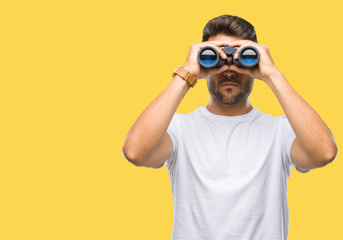 Young handsome man looking through binoculars over isolated background with a confident expression on smart face thinking serious Wall mural