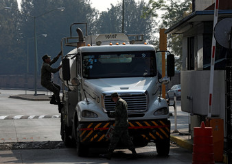 Mexican soldiers inspect a tanker truck transporting fuel before leaving a fuel distribution terminal in Mexico City