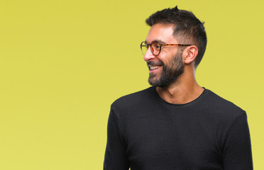 Adult hispanic man wearing glasses over isolated background looking away to side with smile on face, natural expression. Laughing confident. Wall mural