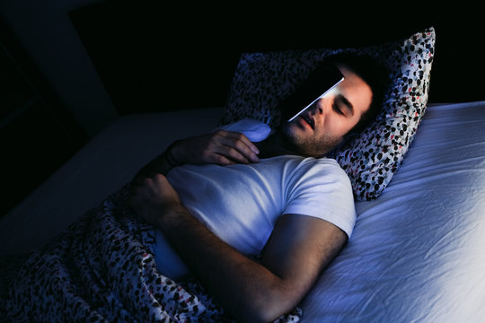 Young man using smartphone in bed at night