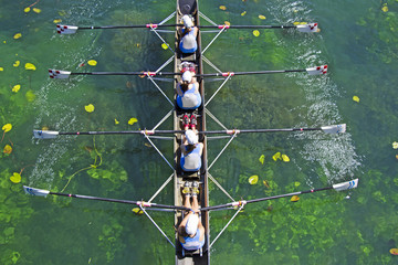 Four Womens rowing team on blue lake, Aerial view