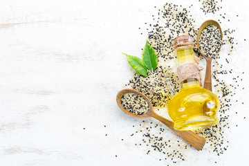 Seeds of sesame and sesame oil. On the old background. Top view. Free copy space.