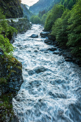 A mountain river flows between the woods of rocks.