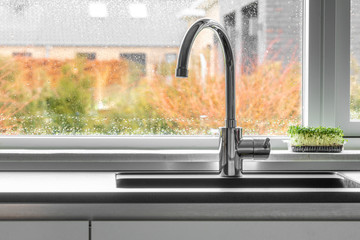 Chrome faucet by a kitchen sink with a wet window